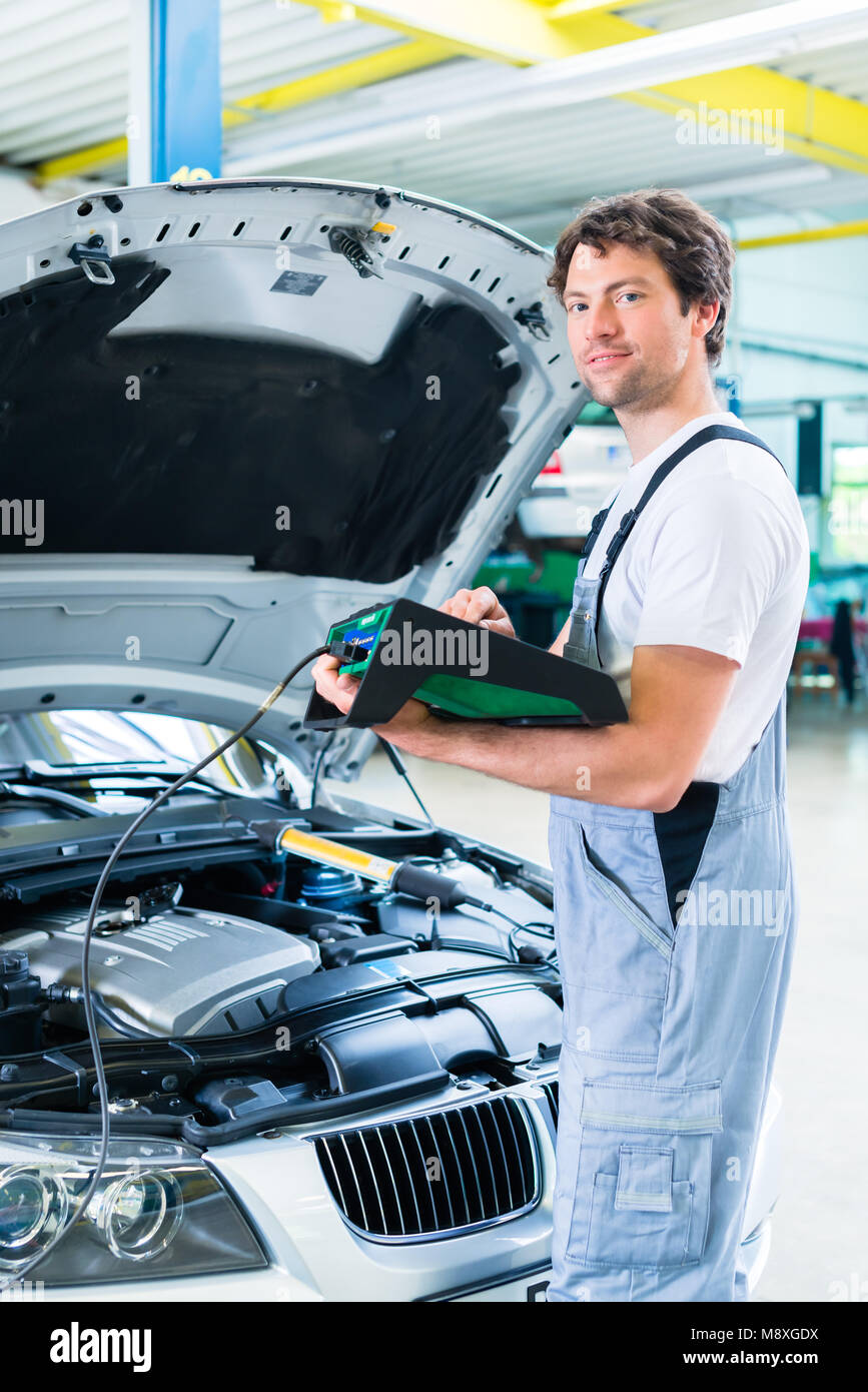Mechanic With Diagnostic Tool In Car Workshop Stock Photo 177604614
