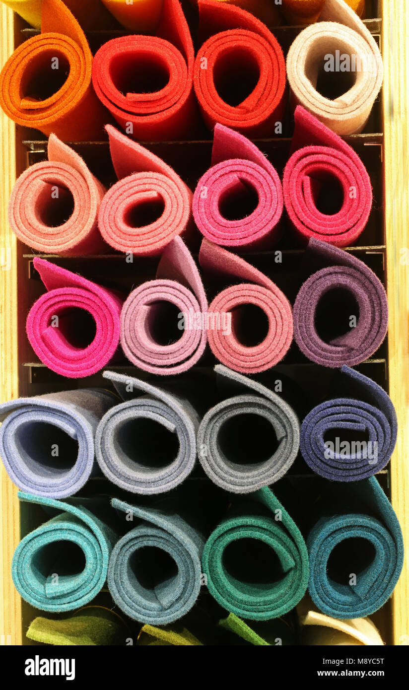 many colored big rolls of fabric in the rack of the tailoring for