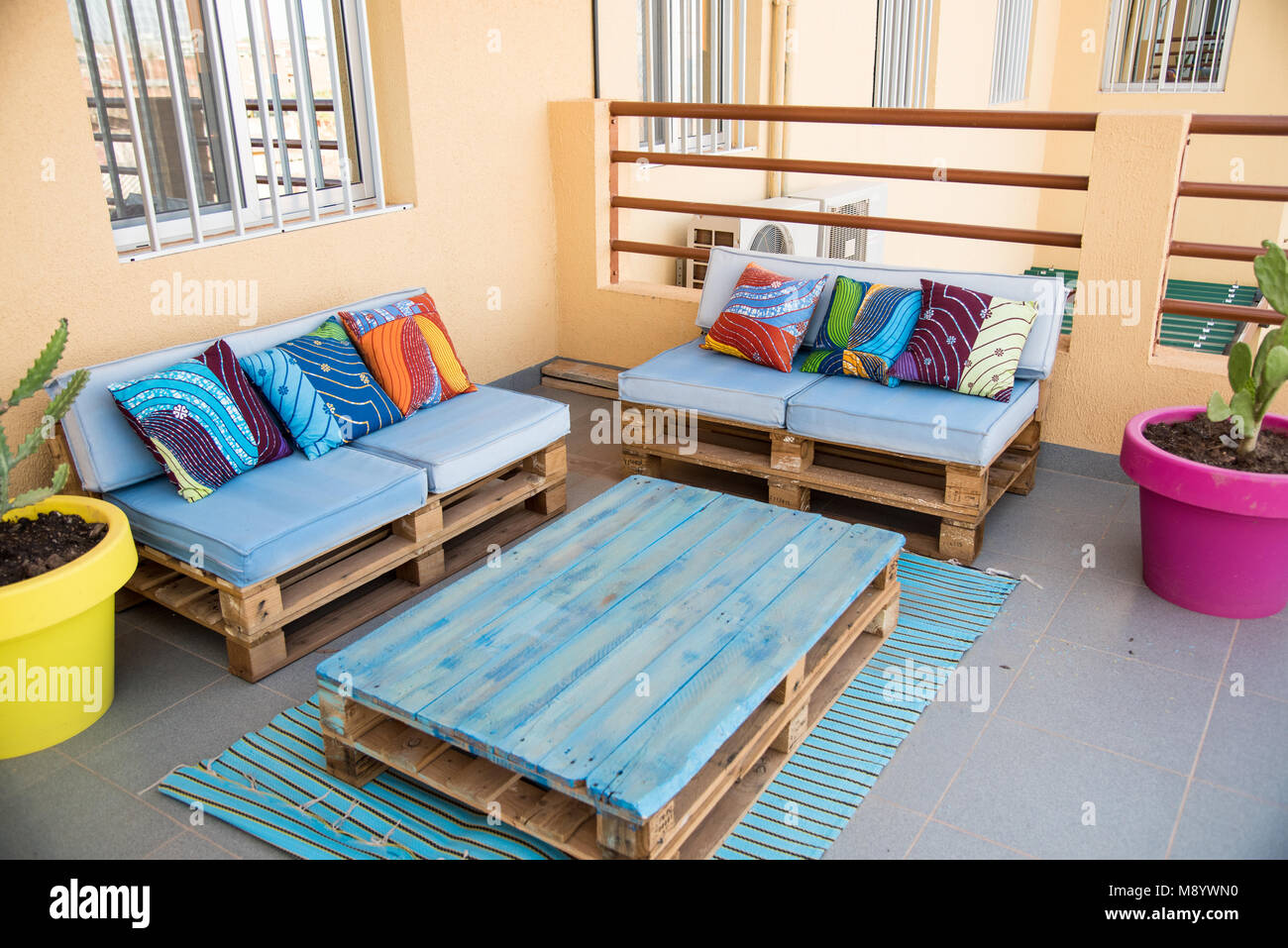 Cool Patio Furniture Made From Wooden Pallets. Painted Blue With Bold,  Colorful African Fabric Throw Pillows. Bright And Happy Space.