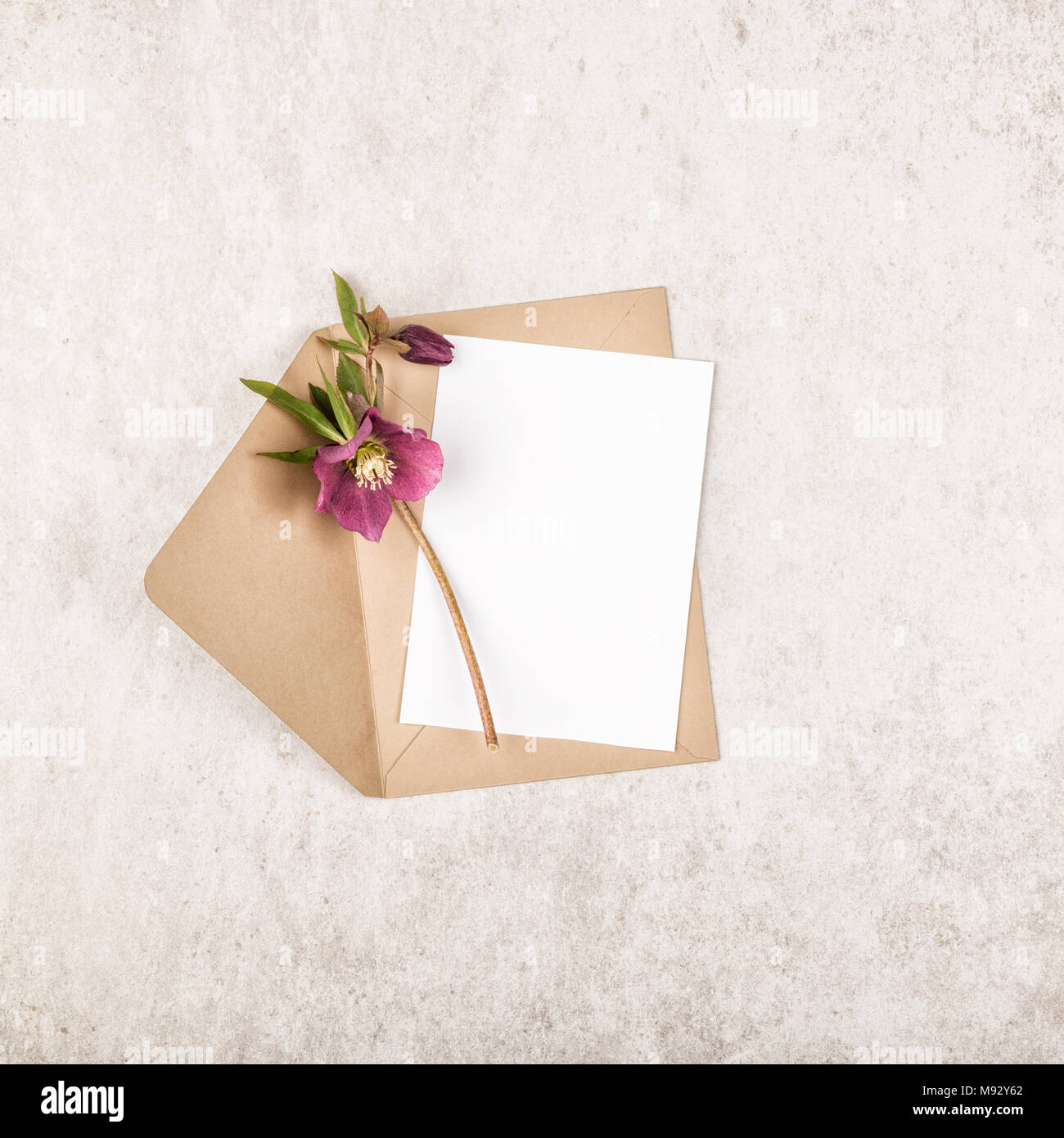 beige craft envelope with blank white note card and bouquet of