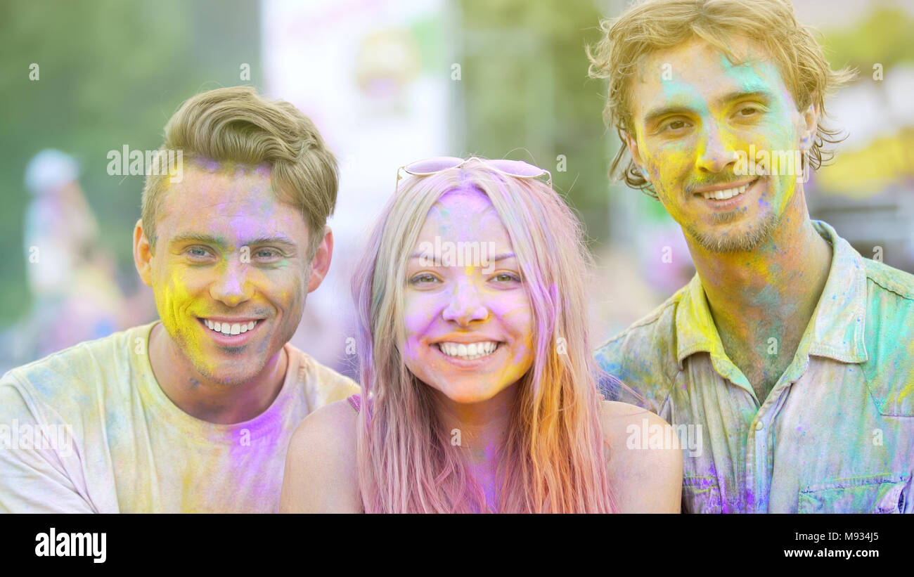 joyful young people smiling to camera color powder on faces having