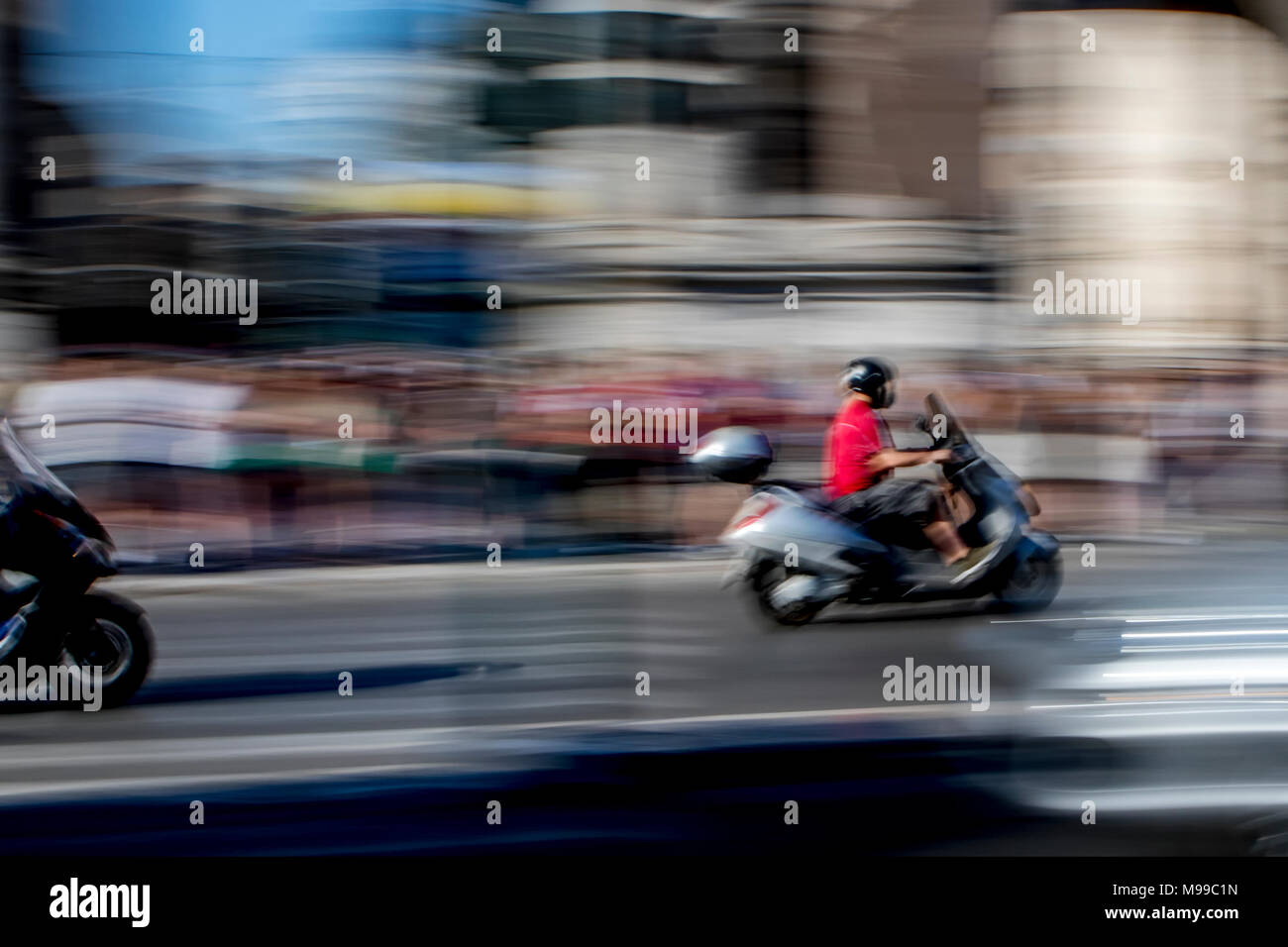 Motorcycle Riders Speeding Along Busy Road In Rome Captured To Show Speed  And Action And Abstract