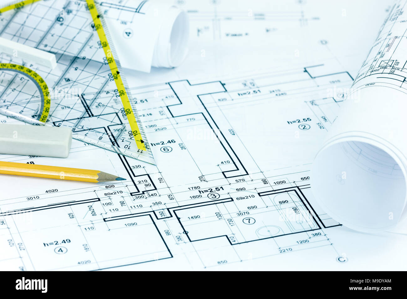 blueprint rolls with architectural plans and drawing instruments on