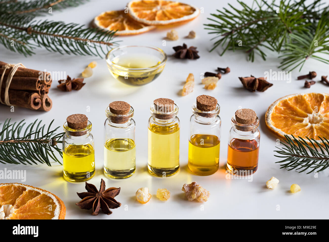 christmas selection of essential oils and spices on white background bottles of essential oil spruce fir frankincense resin star anise cinnamon - Christmas Essential Oils