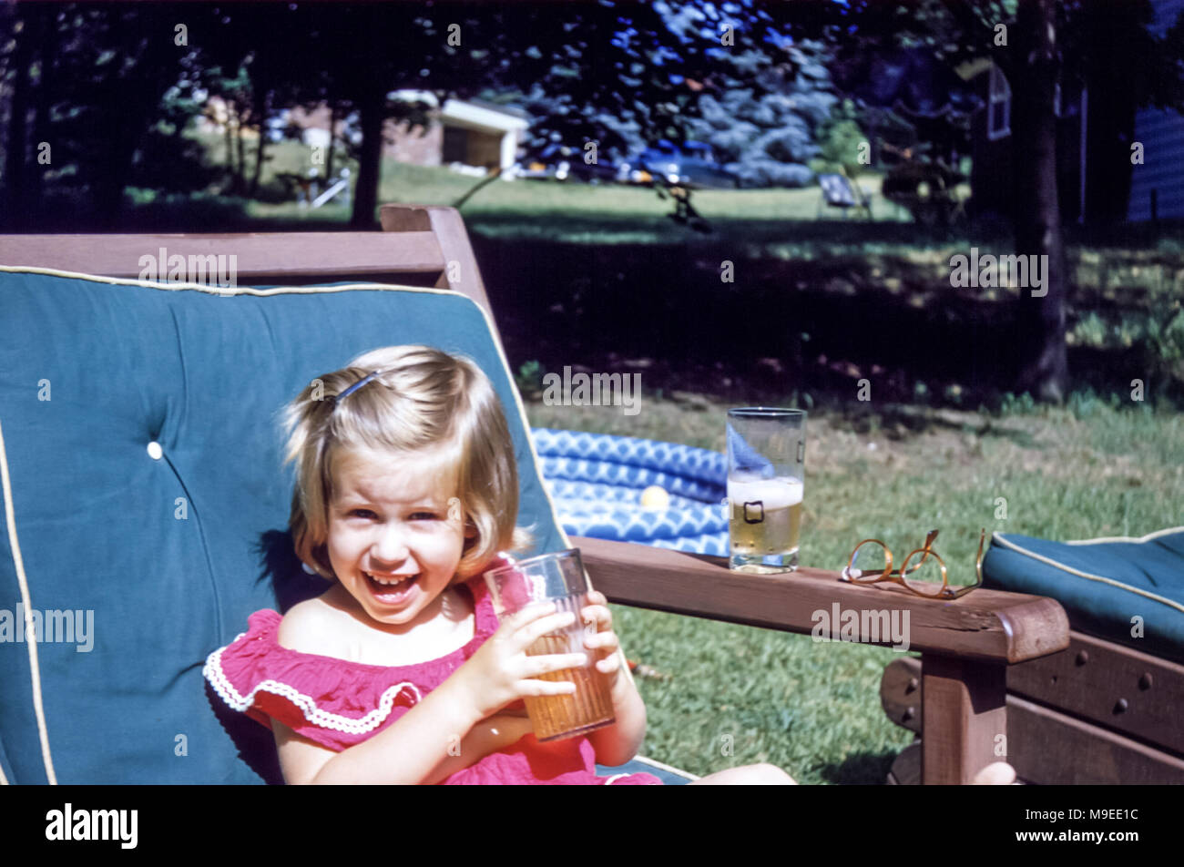 2 To 3 Year Old Smiling Young Girl Sitting In A Garden Chair Holding Plastic Cup Of Juice With Paddling Pool On Summer Day