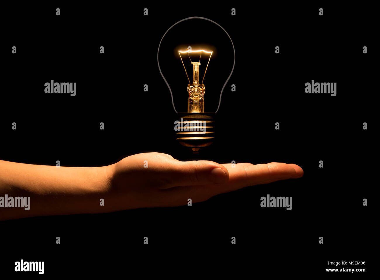 Hand Holding A Filament Lamp On A Black Background The Bulb As A