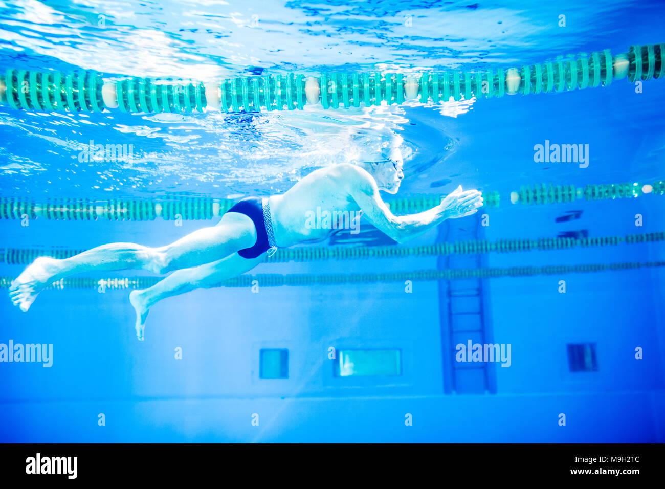 Senior Man Swimming Underwater In An Indoor Pool Active Pensioner Enjoying Sport