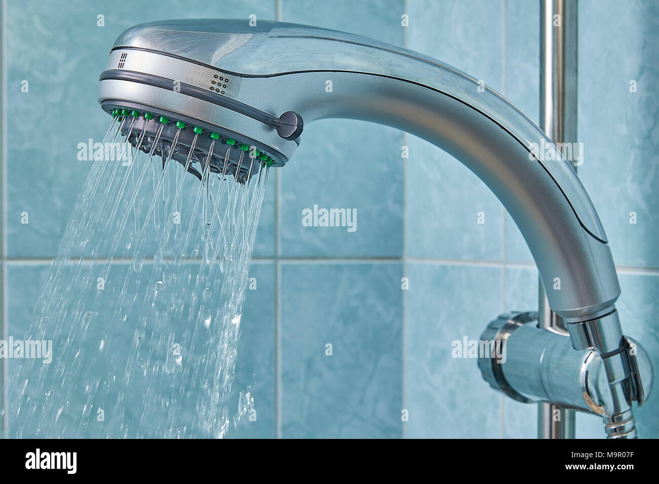 Water runs from the new shower head, which is fixed in the holder in ...