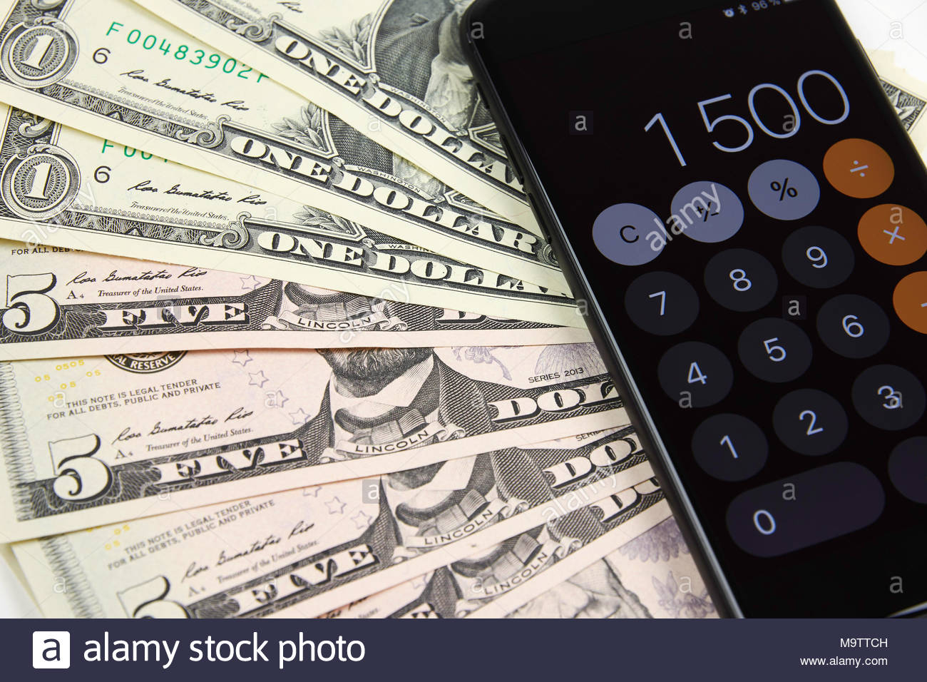 dollar bills with mobile phone with calculator on white desk table