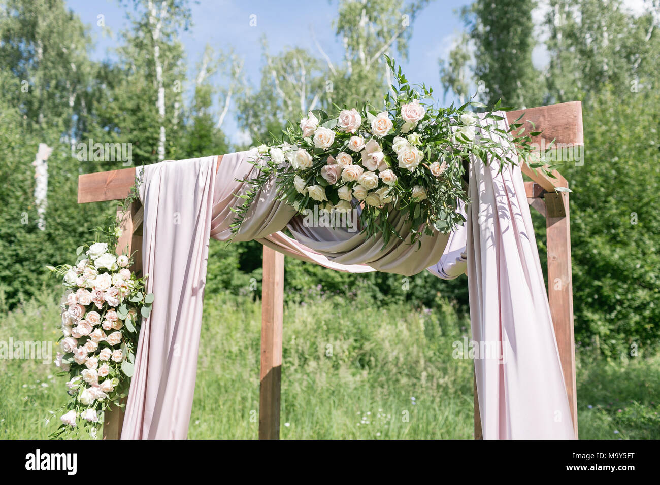 Wooden arch decorated with flowers, are in the zone of the wedding ...