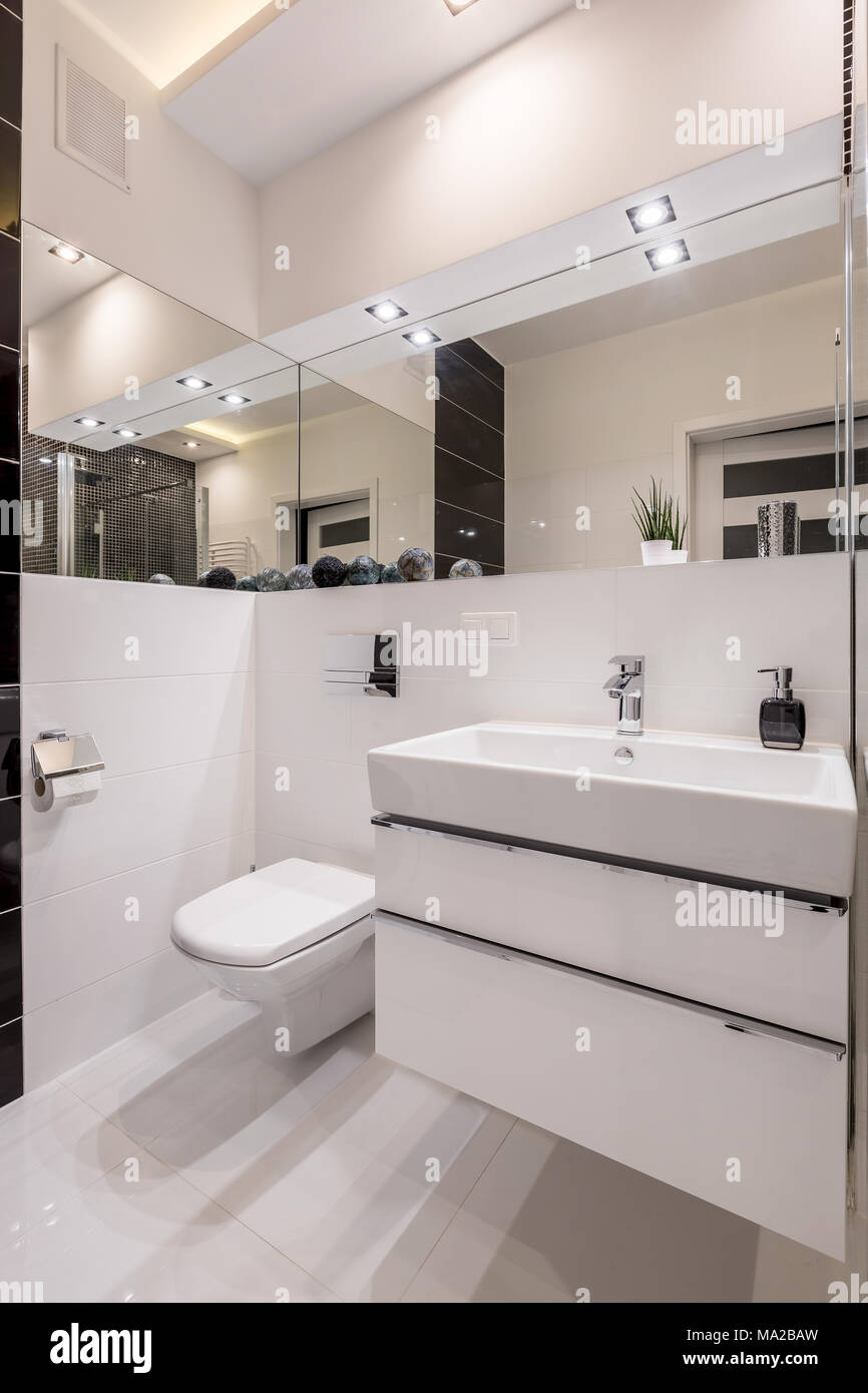 White, mirrored bathroom with cabinet basin, toilet and led lighting ...