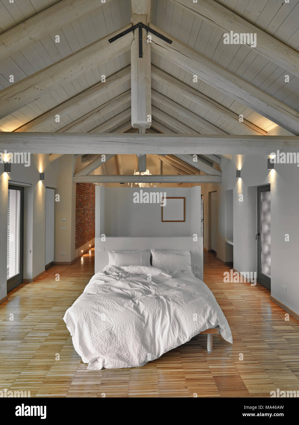 modern bedroom in the attic room with wooden ceiling and wooden