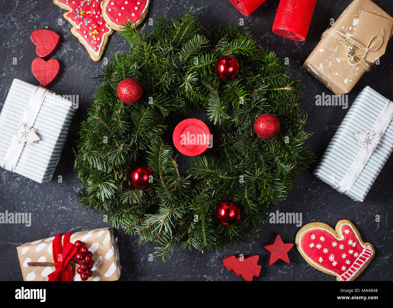 Christmas wreath and Christmas gifts on a black stone surface. Top ...