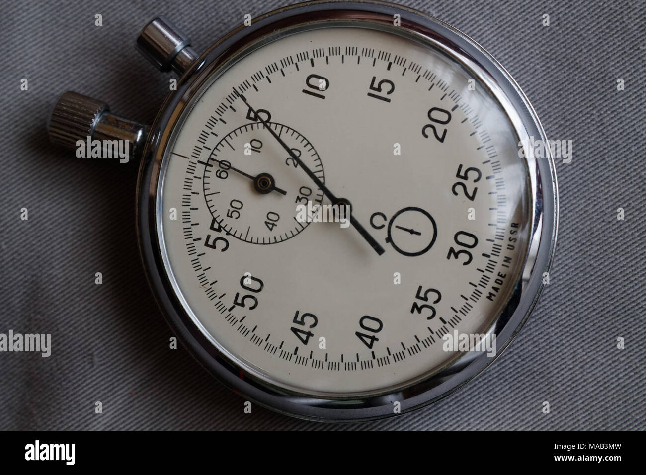 stopwatch on white denim background value measure time old clock