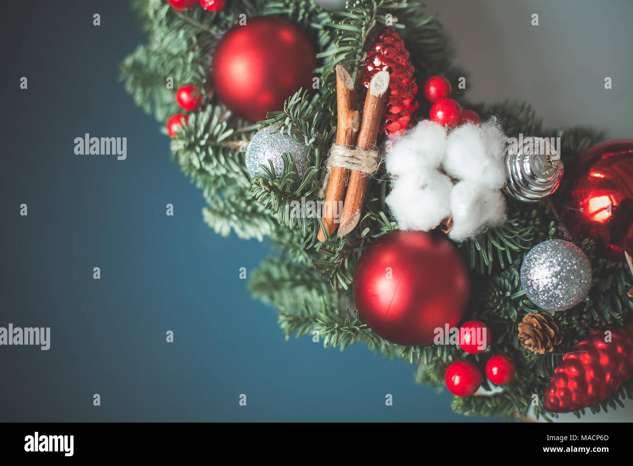 christmas background with xmas tree twig glass balls and new year holly berries on blue