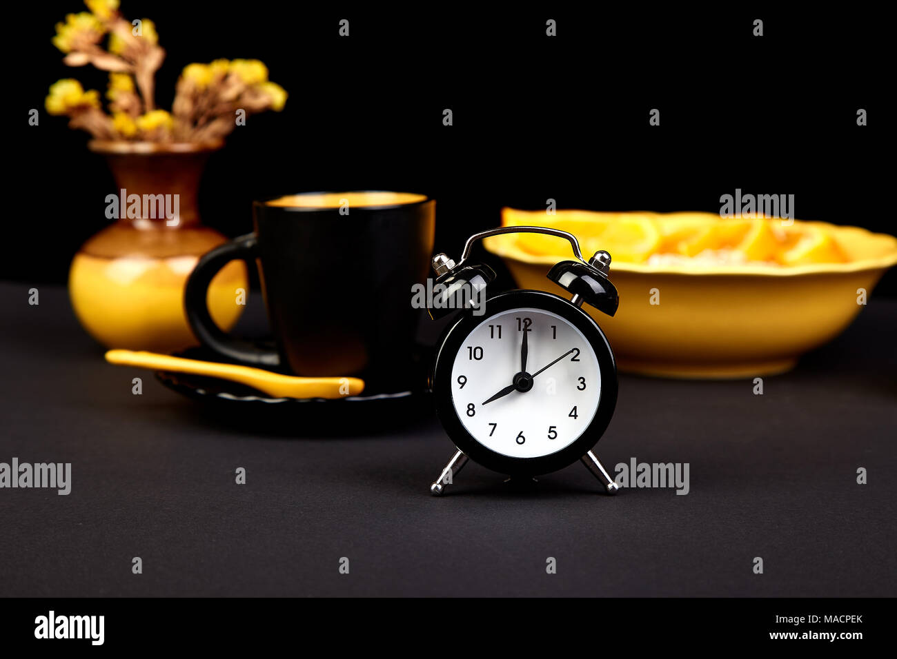 morning coffee granola breakfast with fruit near alarm clock
