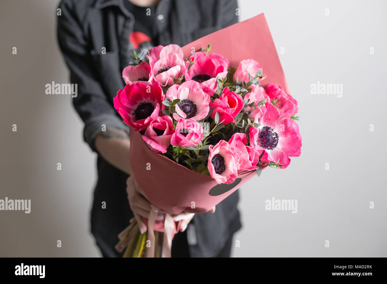 Cute flowers beautiful bouquet of pink anemones in woman hand the cute flowers beautiful bouquet of pink anemones in woman hand the work of the florist at a flower shop a small family business izmirmasajfo
