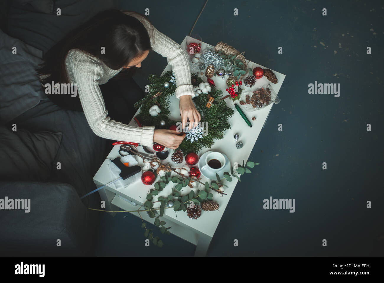 florist woman making christmas decorations at home office desk