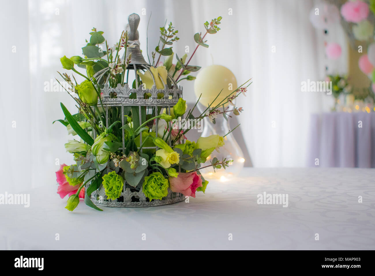 Flowers In Birds Cage On White Table Decoration Stock Photo