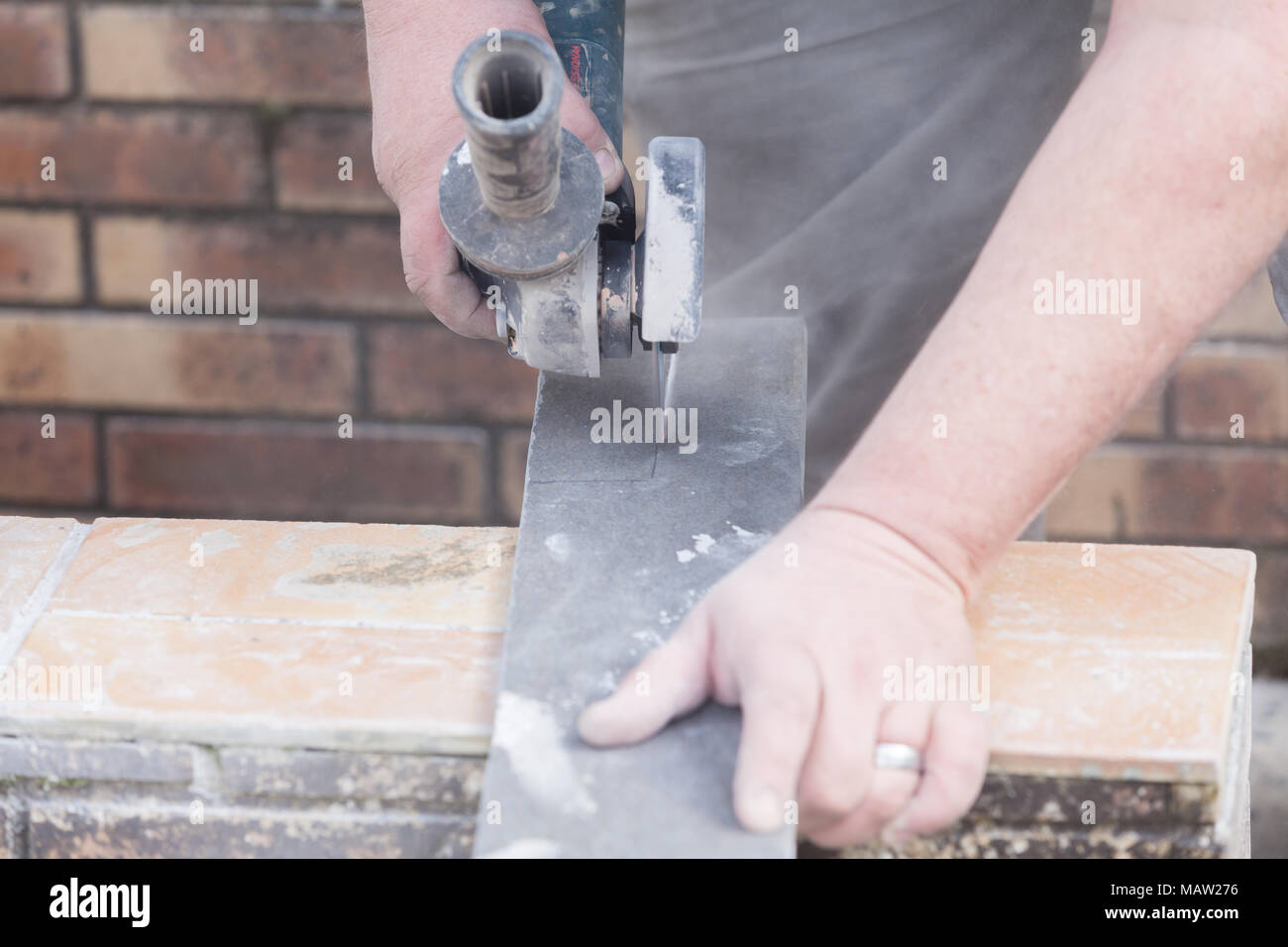 Electric tile cutter stock photos electric tile cutter stock tiler cutting a tile with a grinder stock image dailygadgetfo Images