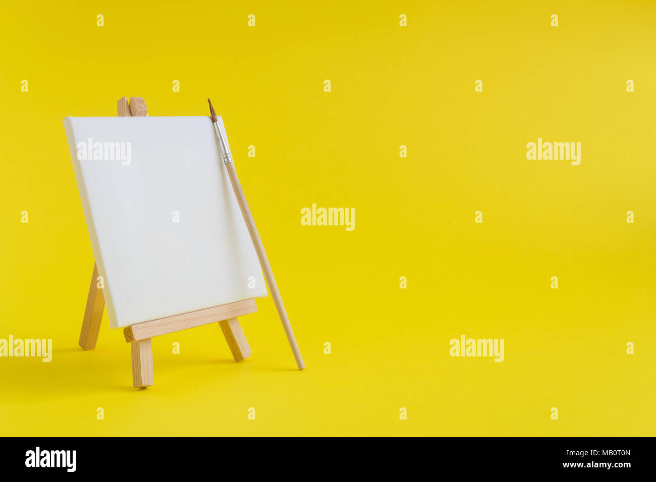 Blank art canvas on easel and paintbrush against yellow background ...
