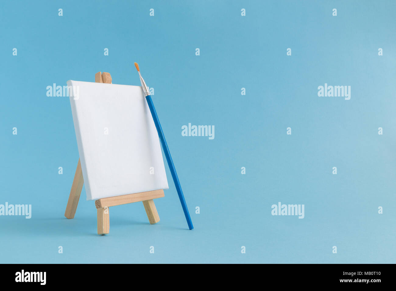 blank art canvas on easel and paintbrush against pastel blue