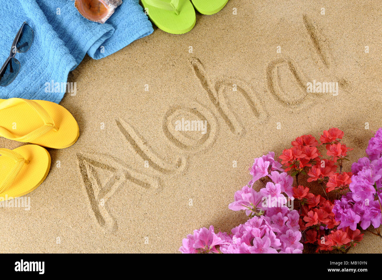the word aloha written in soft sand with flip flops flowers and