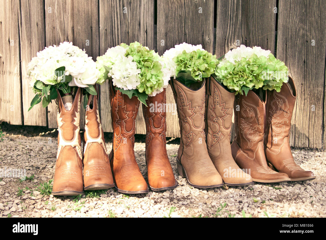Cowboy Boots And Bouquets Are Lined Up By A Grey Barn At A Country