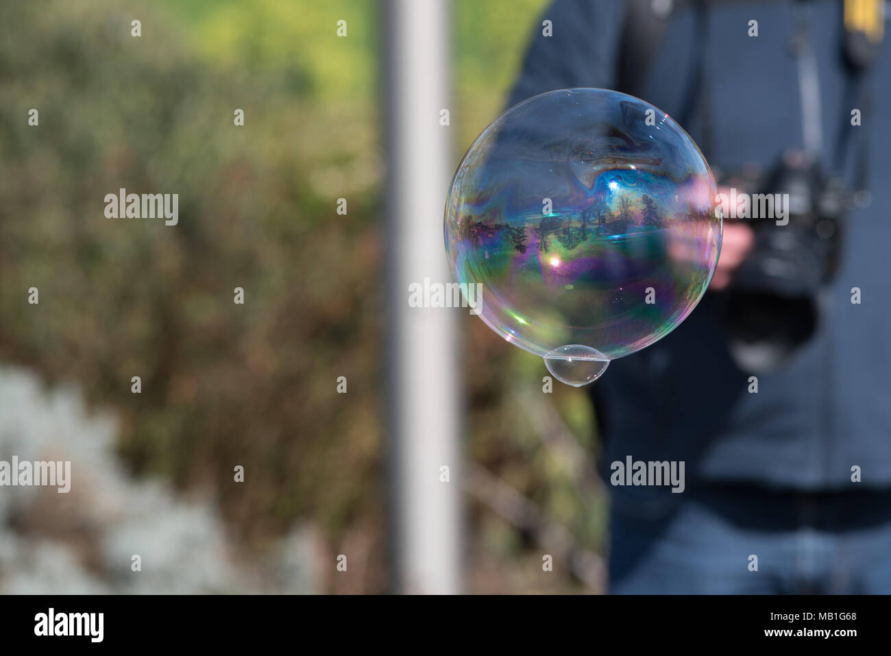 Bubble With Reflection Of Trees And Water And Person With Dslr In