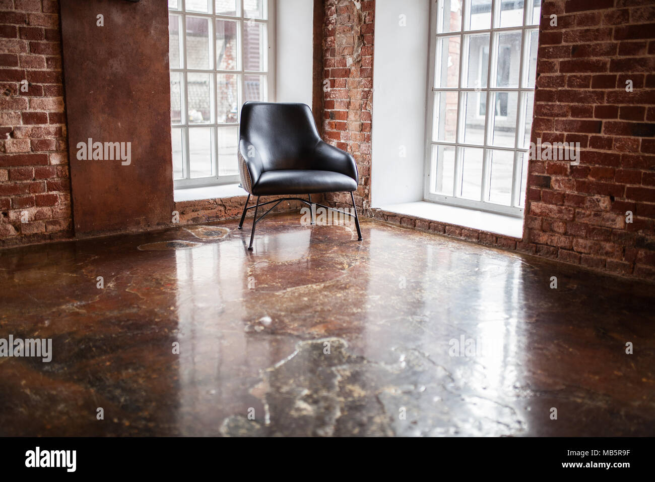 Chair Stands Near A Window On The Brick Wall Background In The Windows Loft  Style