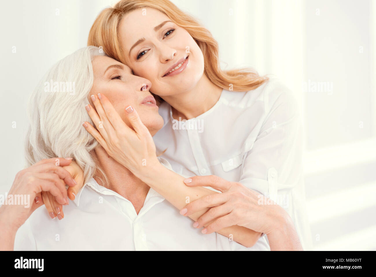 loving daughter hugging her senior mom at home stock photo