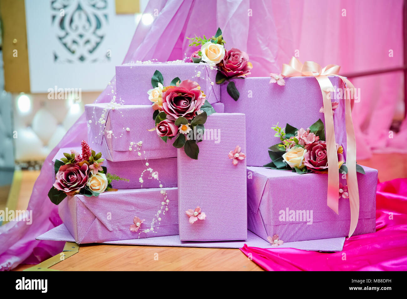 Stack of violet gift boxes . Purple gift boxes with white and red ...