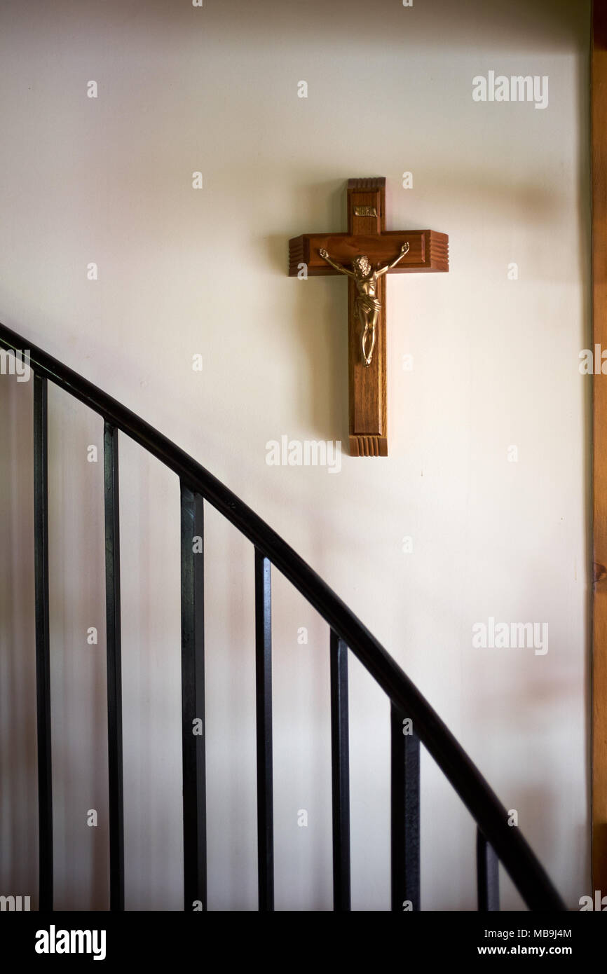 Wooden Crucifix With Figure Of The Crucified Christ Hanging On A White  Interior Wall With Stair Bannister