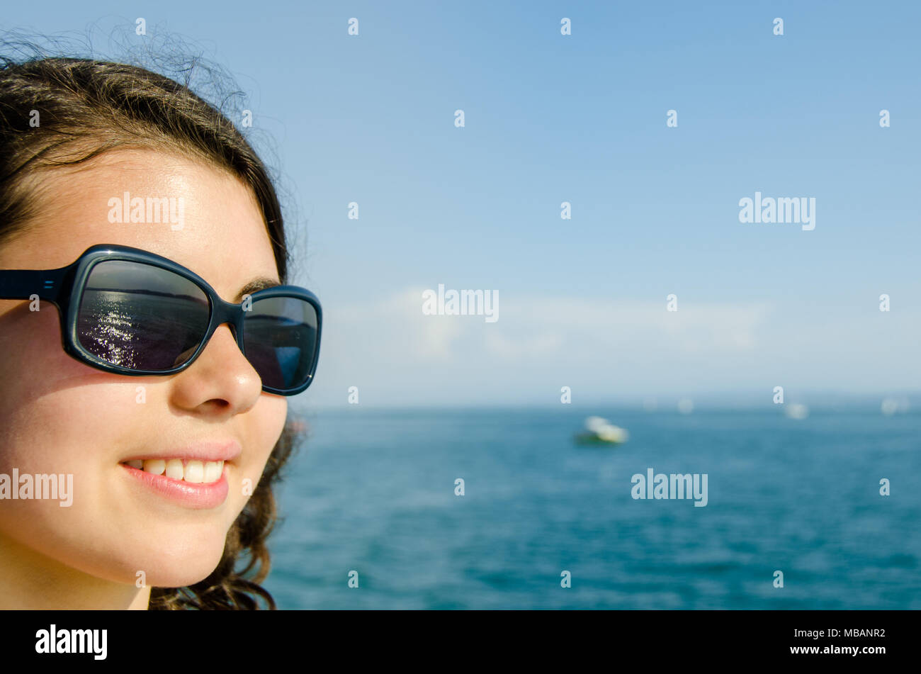 02fe9005b2 Portrait of happy young woman with sunglasses at the beach looking on copy  space with boats in the background