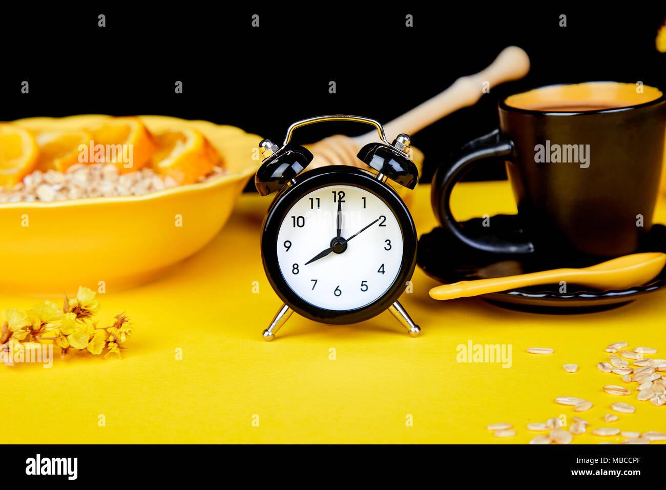 morning coffee granola breakfast with fruit near black alarm clock