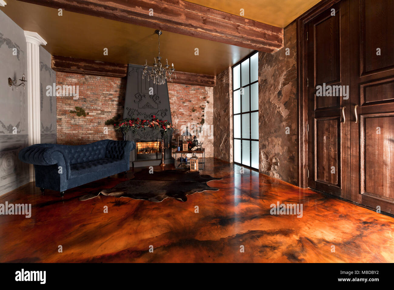Interior with fireplace candles skin of cows brick wall large window and a living room coffee table and dark blue sofa in modern design. & loft style. Interior with fireplace candles skin of cows brick ...