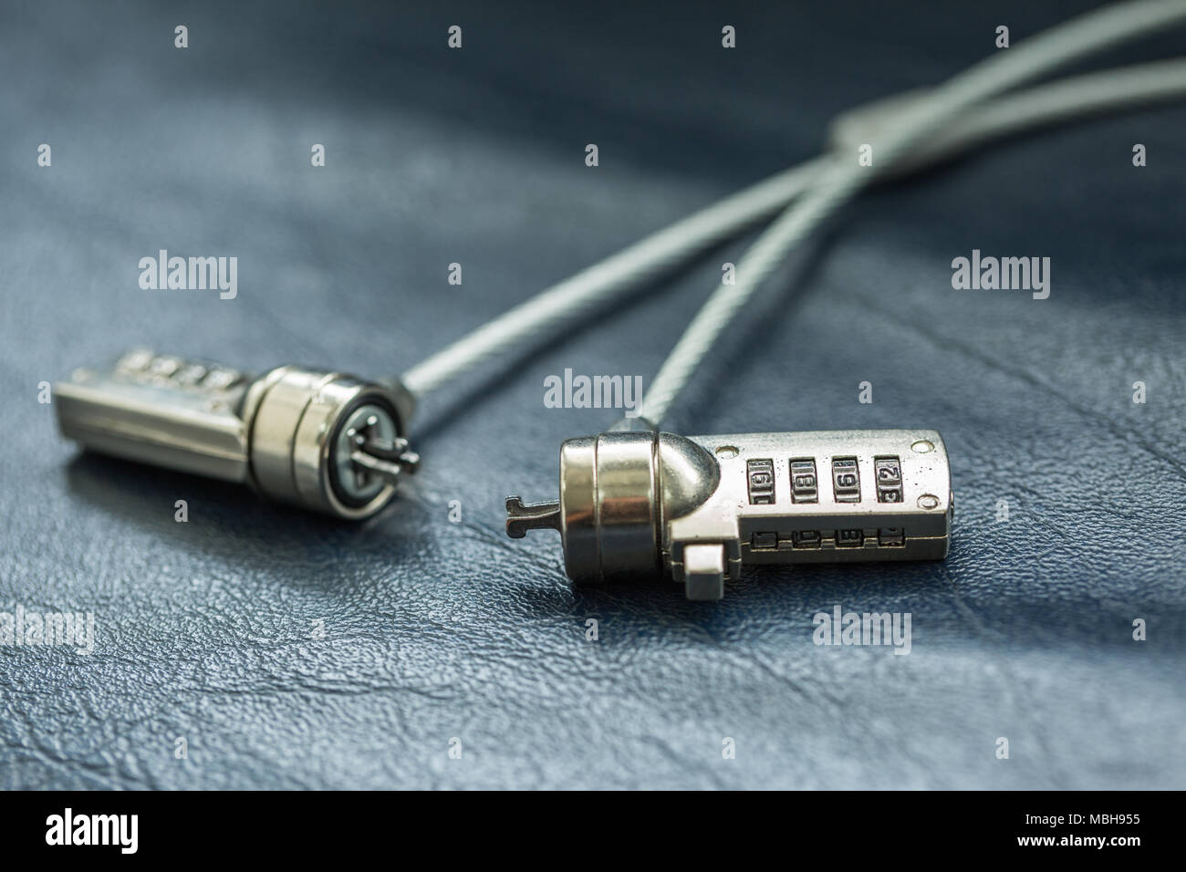 Two computer cable lock on black leather, Security concept shot for ...