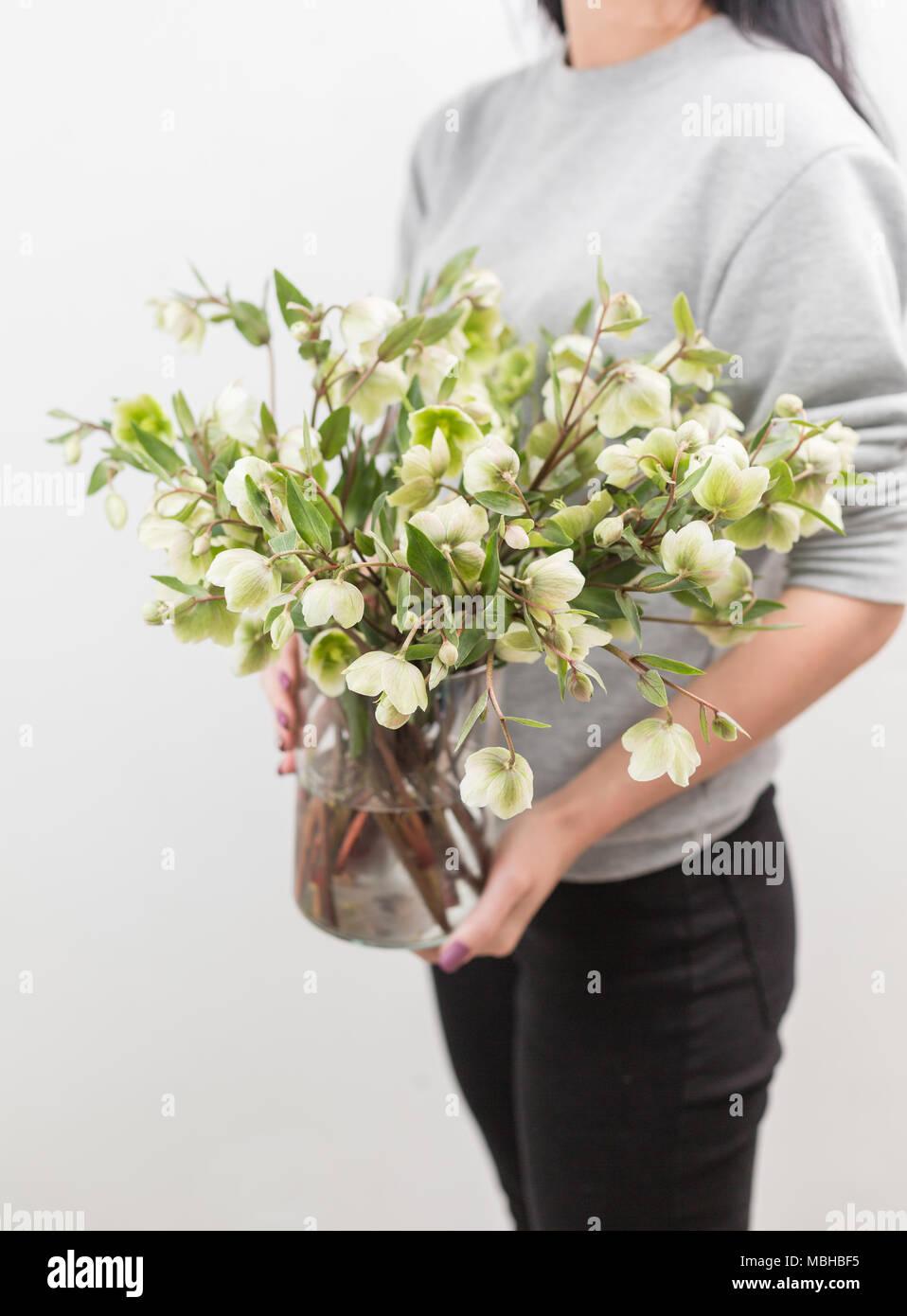 Bouquet of beautiful green helleborus winter flowers in woman hand bouquet of beautiful green helleborus winter flowers in woman hand the work of the florist at a flower shop vertical photo izmirmasajfo