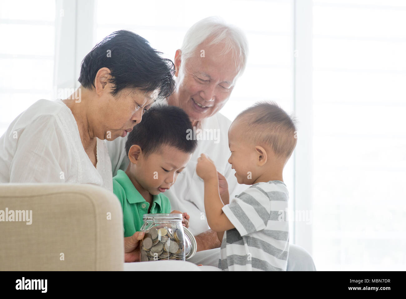 asian old people and children saving money at home family financial