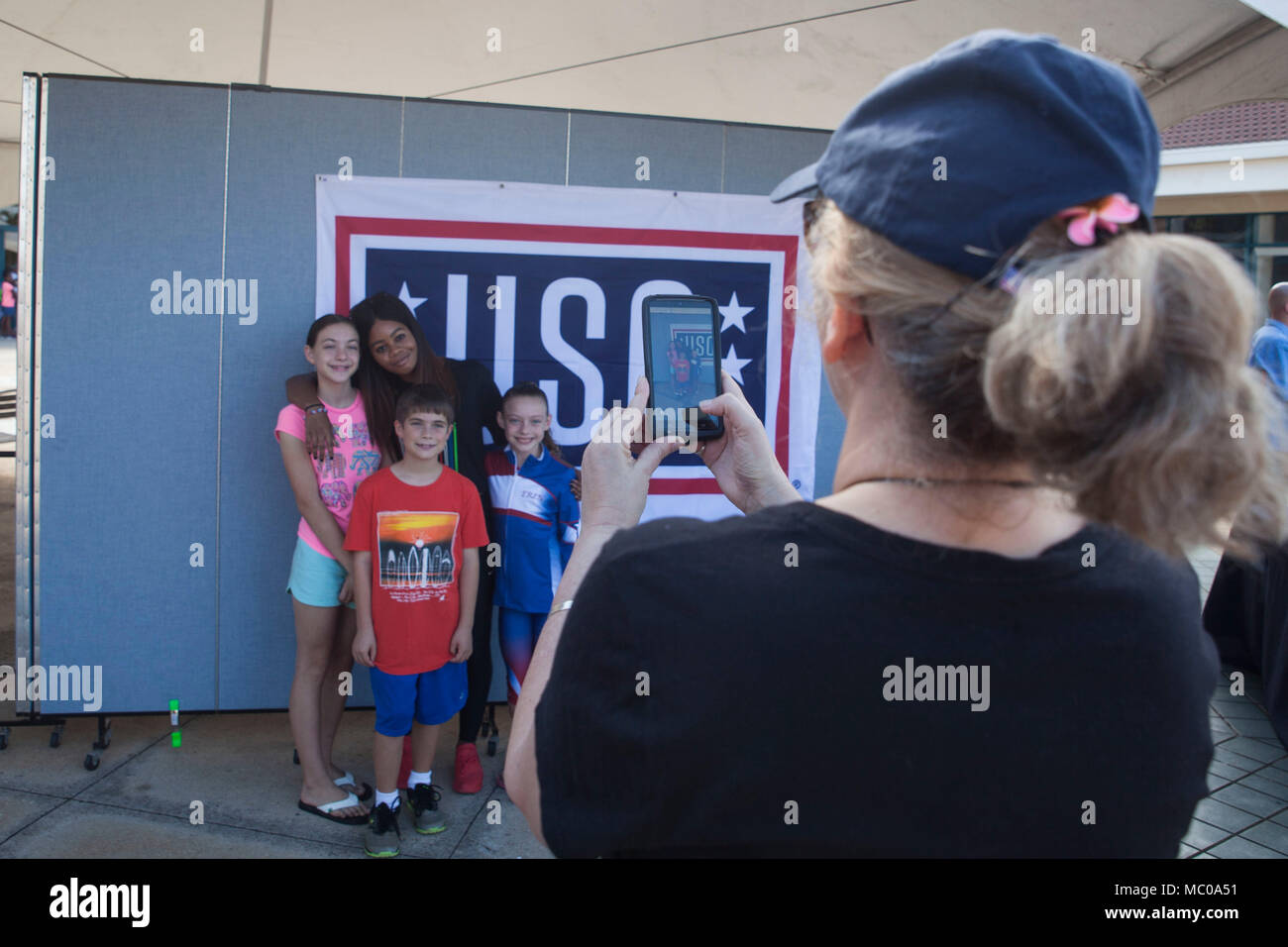 Young fans pose for a photo with gabrielle gabby douglas during a young fans pose for a photo with gabrielle gabby douglas during a united services organization uso meet and greet event at the mokapu mall marine corps m4hsunfo