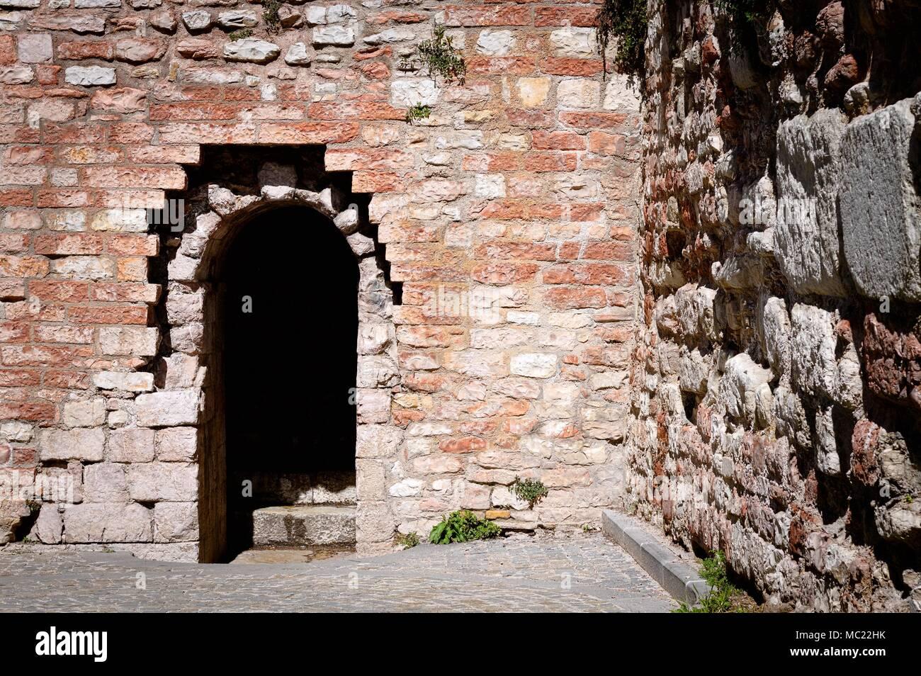 entrance of a castle round arch and brick walls spello umbria