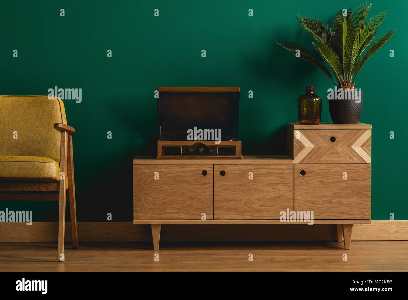 Close Up Of A Retro Wooden Dresser With A Hipster Record Player In A  Minimalist Dark Green Living Room Interior