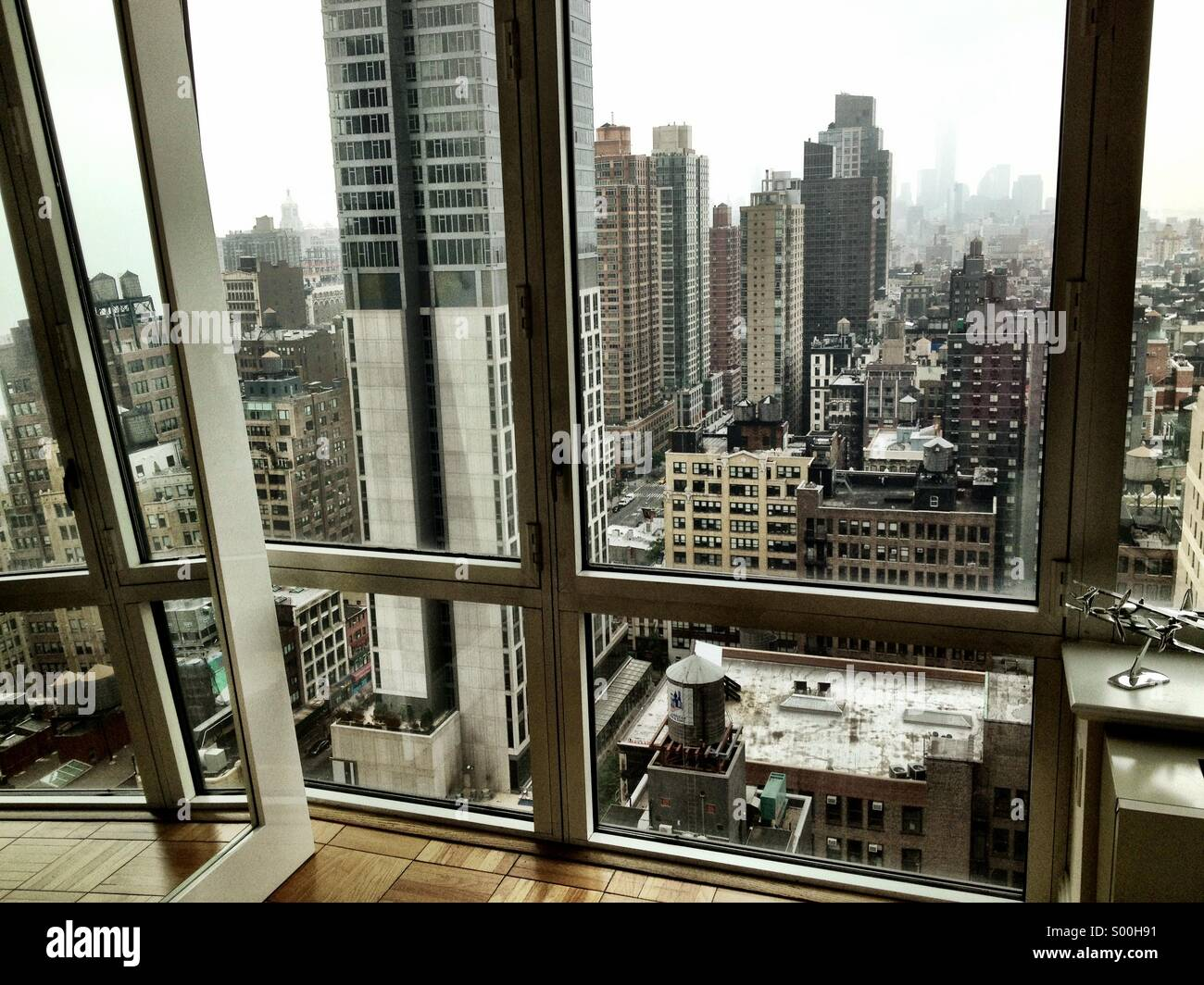 view of lower manhattan out the window of a luxury high-rise stock