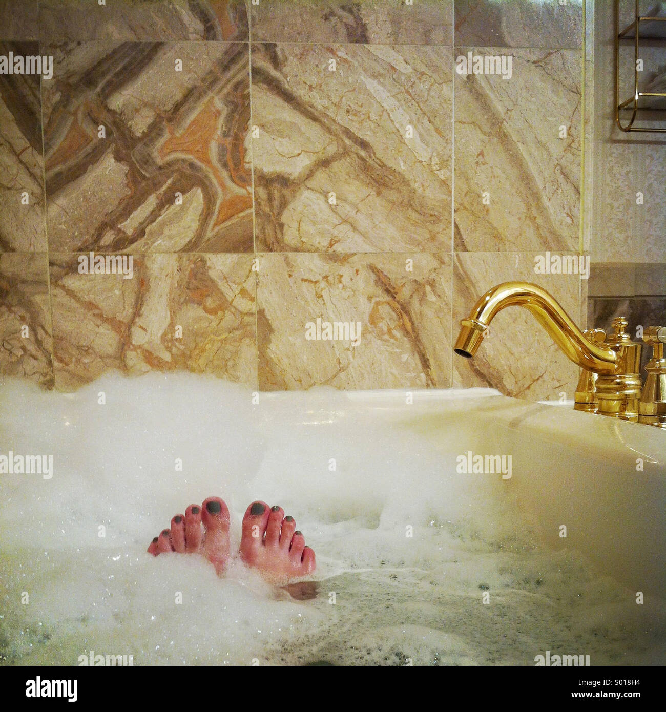 A woman\'s toes peek out from a relaxing bubble bath in a fancy ...
