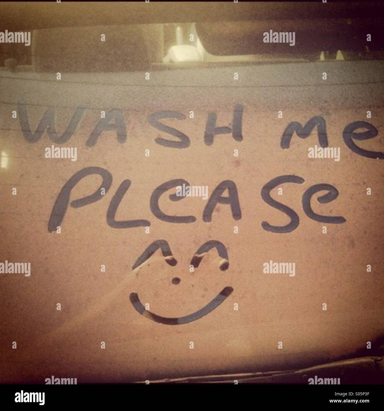 Wash Me Please Written Into Dirt On A Car Window Stock Photo
