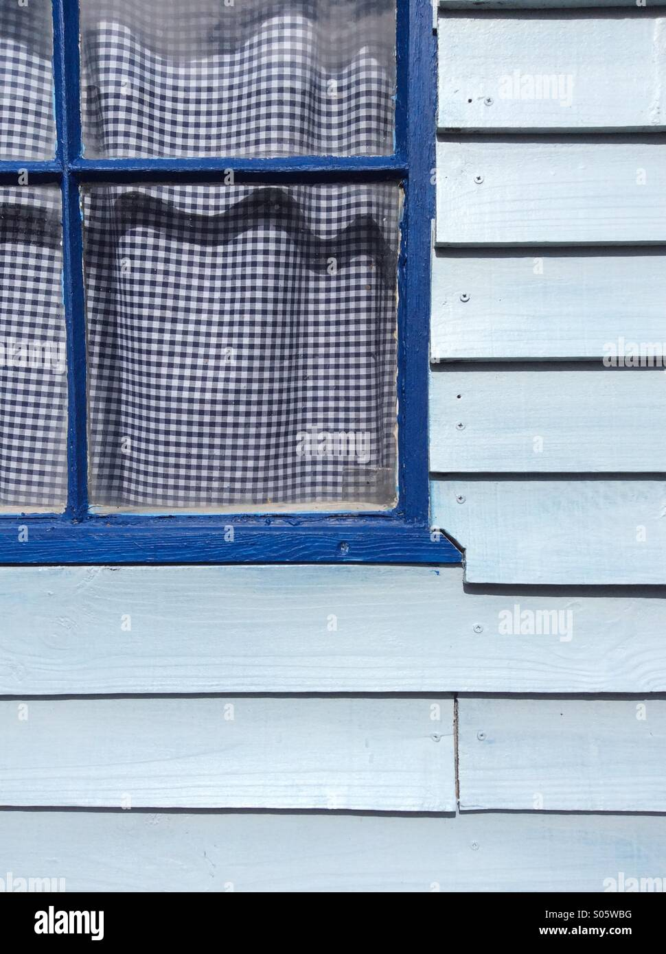Blue Clapboard Shed With Blue Window Frame And Blue Gingham Curtains.