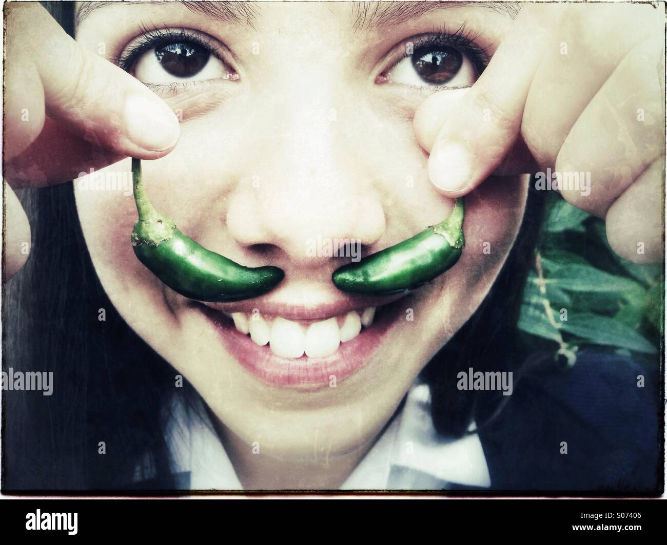 Happy_girl_holds_green_chilies_as_fake_m