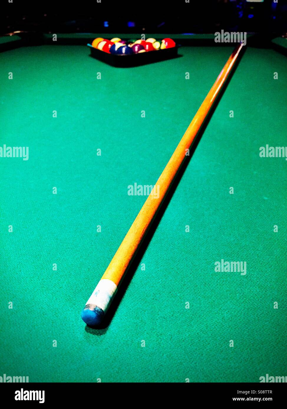 Pool Cue On The Green Felt Of A Pool Table With The Balls Racked.