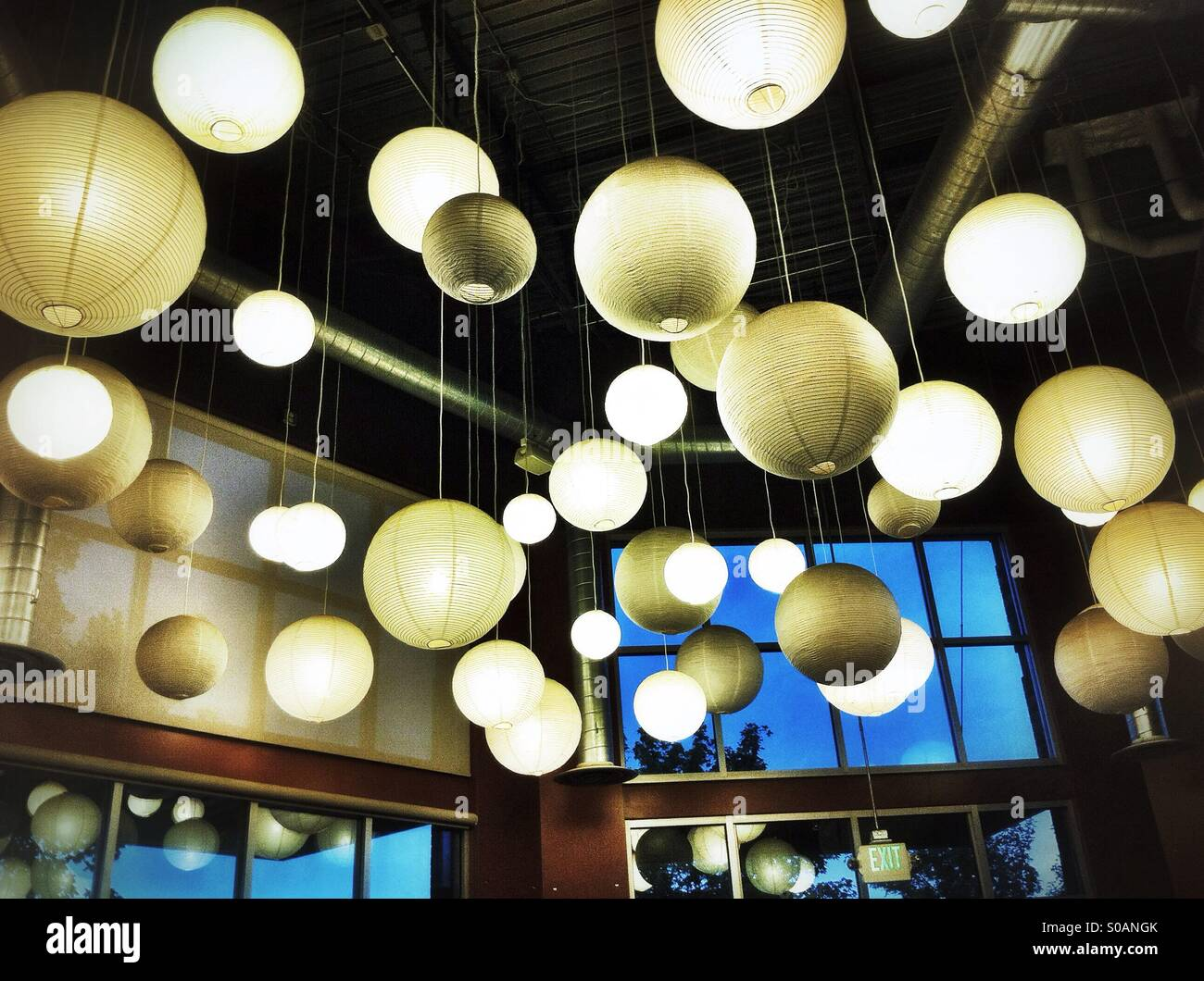 Dozens of white round paper lanterns hanging from the ceiling