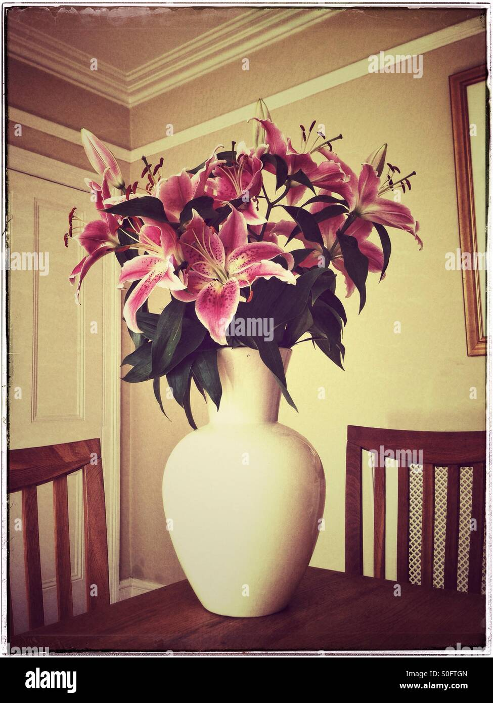 A large flower vase containing stargazer lilies sitting on a a large flower vase containing stargazer lilies sitting on a wooden dining table surrounded by 2 chairs inside a dining room reviewsmspy
